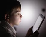 A kid using an iPad to learn