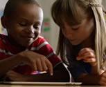 A teacher and a kid using an iPad to learn