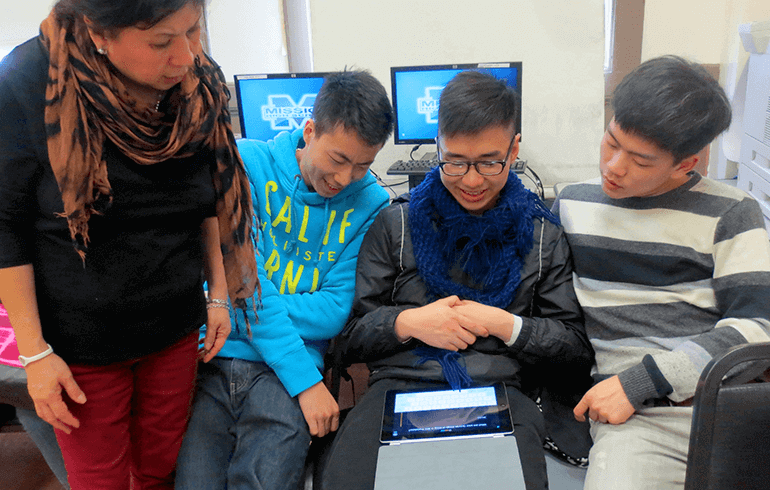 Students holding an iPad and looking at a lesson